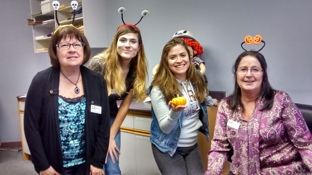 Four women are ready with halloween headgear and a tiny pumpkin