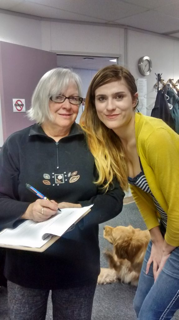 Two women pose with a dog in the background