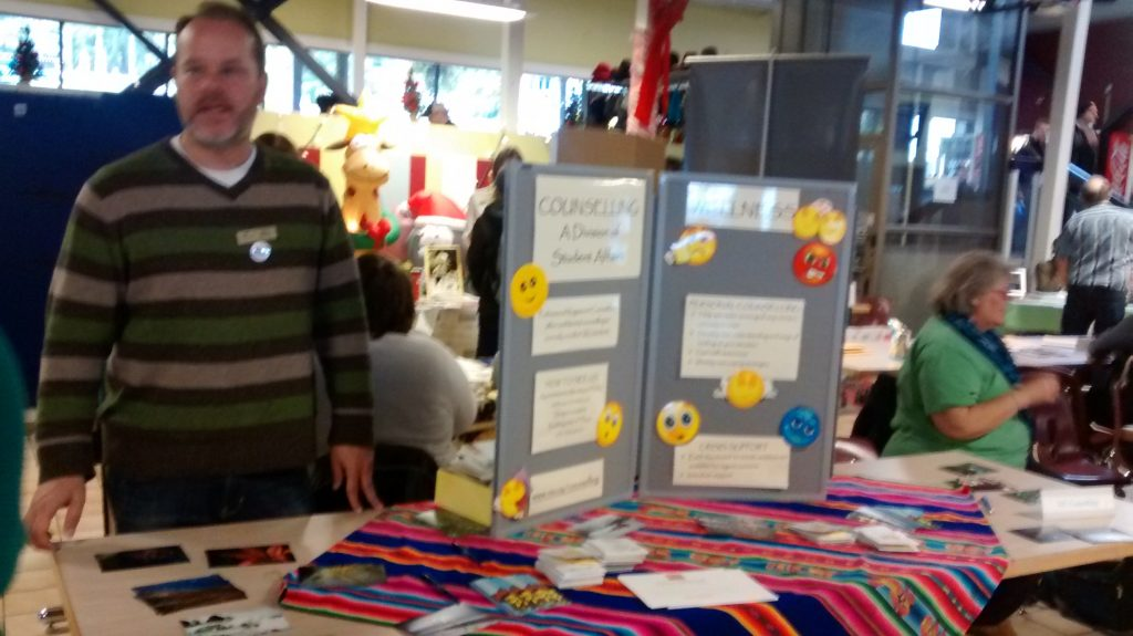 A man in VIU's cafeteria at a booth for NDRC including a posterboard with emojis on it for counselling and wellness.