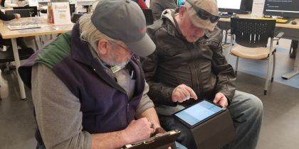 a volunteer and student look over a tablet together