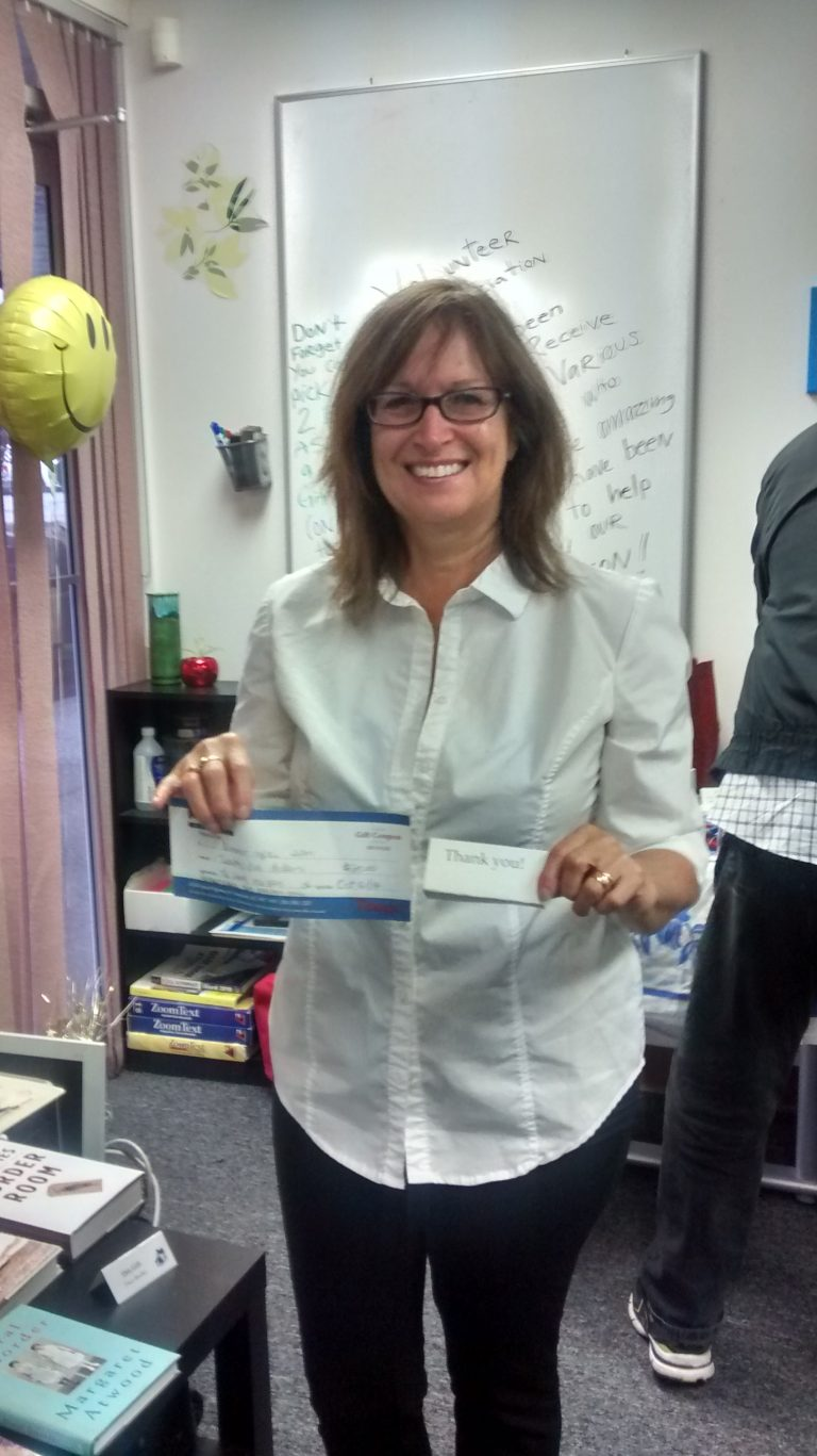 A woman holds up a gift certificate she won