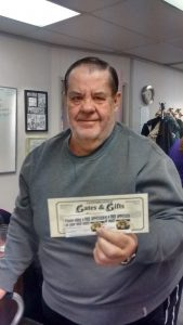 A man holds a gift certificate and some coupons