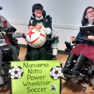 Three people pose with a soccer ball and a sign that says Nanaimo Nitro Power Wheelchair Soccer