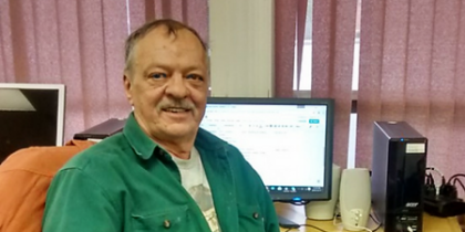 A man looks proud in front of a computer.