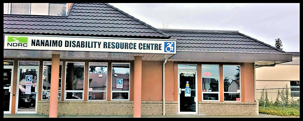 External view of the Nanaimo Disability Resource Center, a tan building with a sign with Nanaimo Disability Resource Centre followed by the updated version of the person with disabilities icon