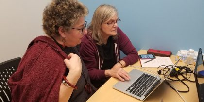 two ladies, one volunteer, one student both look over a laptop