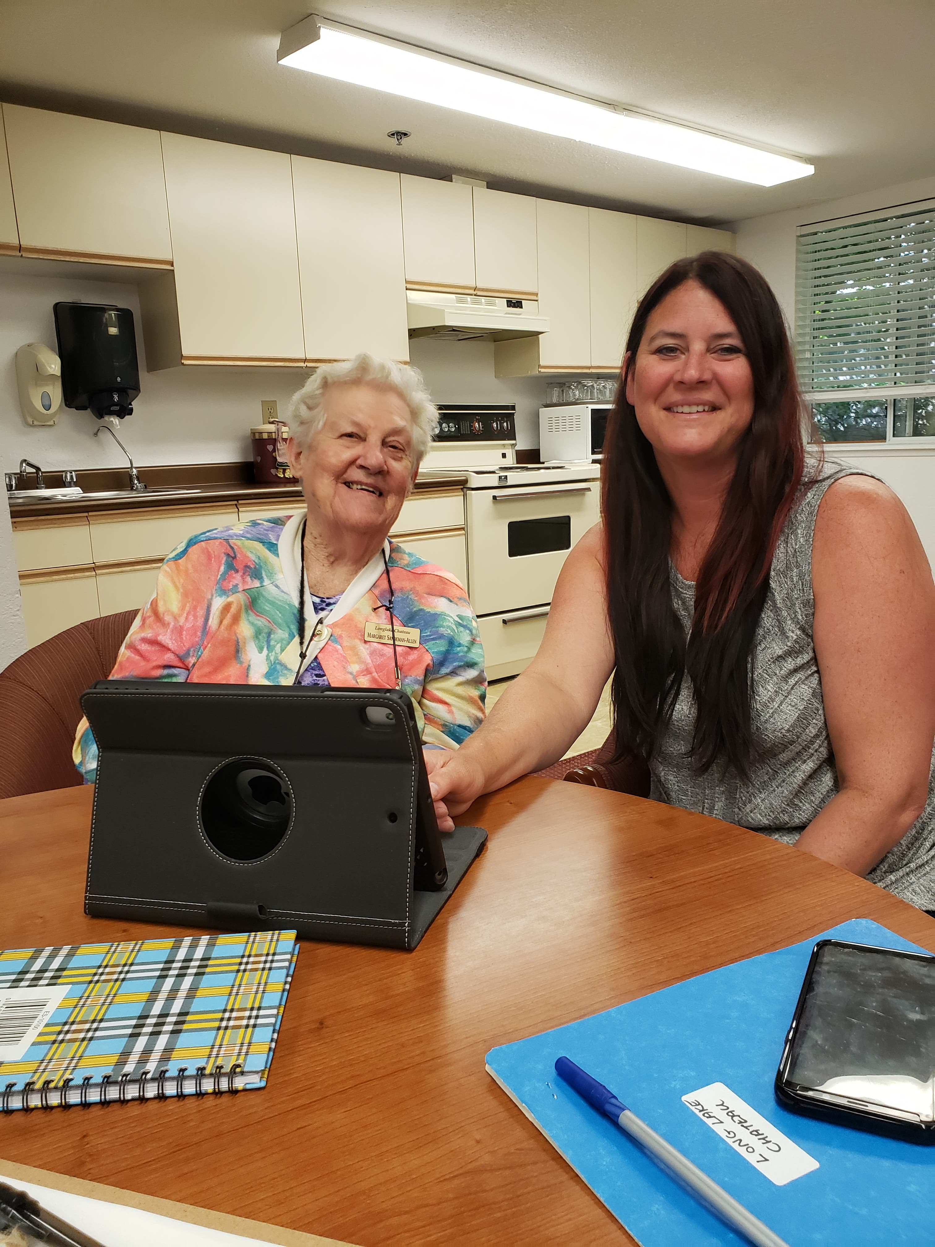 a senior lady sitting with a younger woman in front of a tablet, smiling